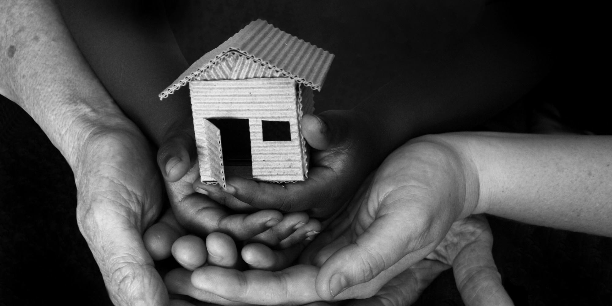 Image of multiple hands holding a home.